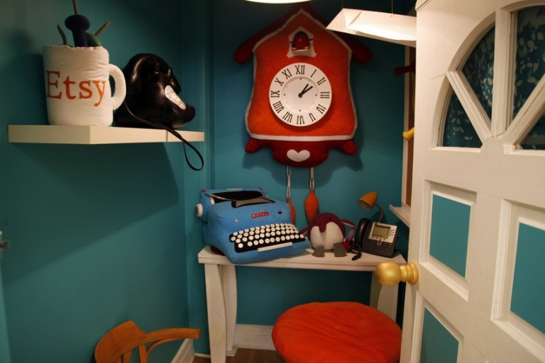 Several brightly painted, cabinet-sized booths designed for making phone calls are stuffed with plush toys
