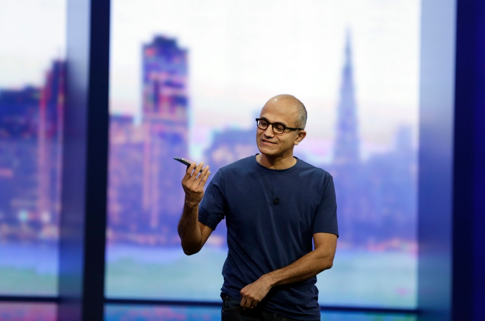 Microsoft CEO Satya Nadella looks over the new Nokia Lumia 930 phone during the keynote address of the Build Conference Wednesday, April 2, 2014, in San Francisco.  Microsoft kicked off its annual conference for software developers, with new updates to the Windows 8 operating system and upcoming features for Windows Phone and Xbox. (AP Photo/Eric Risberg)