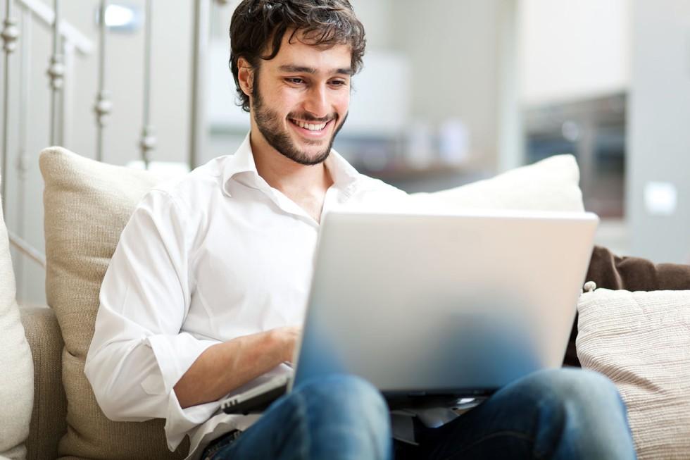 Man-happily-typing-on-laptop